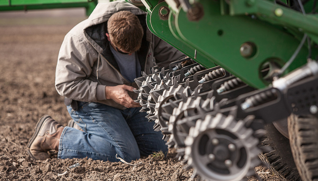 A farmer adjusting a row cleaner while in the field.
