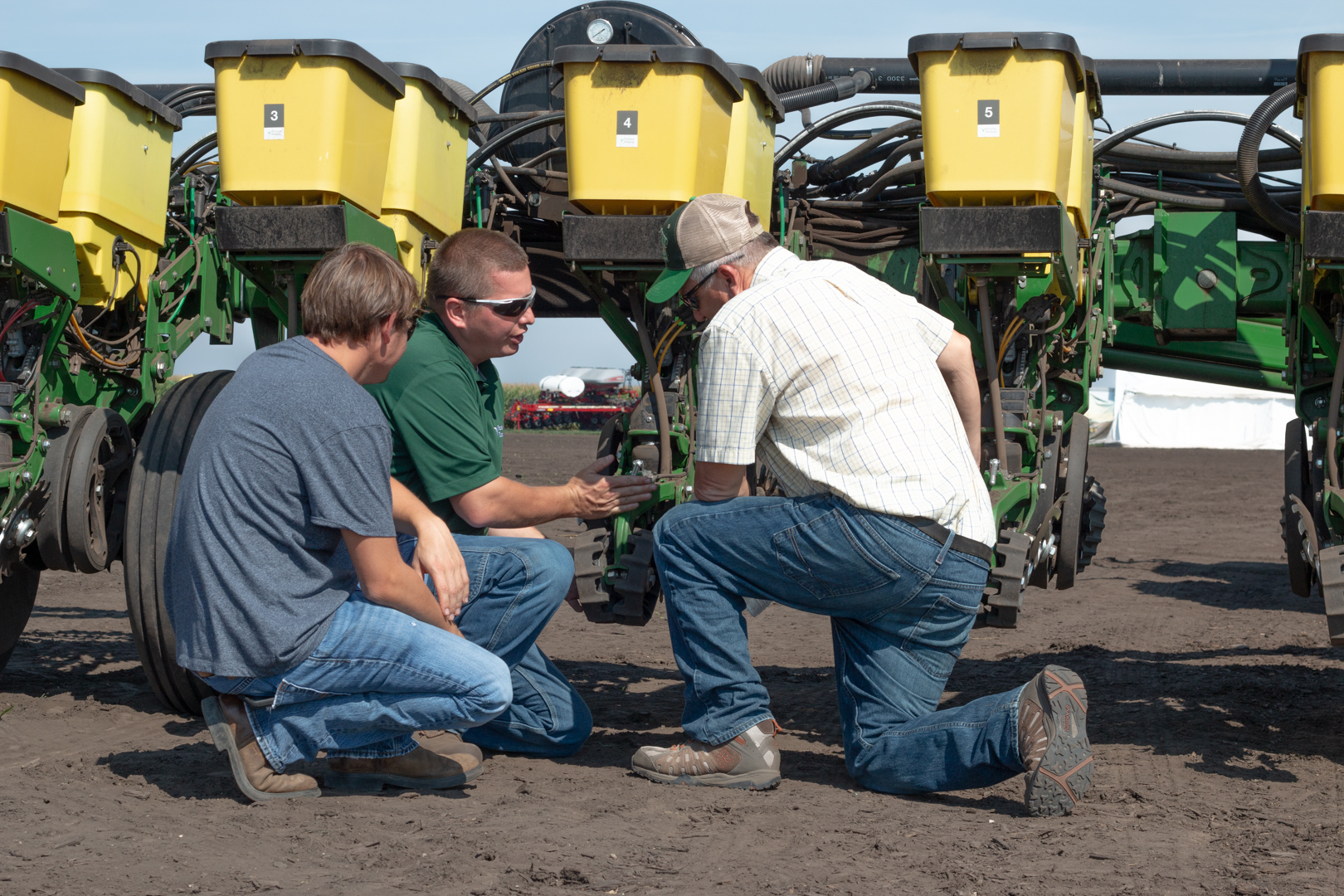 Farmers behind a planter looking at technology.