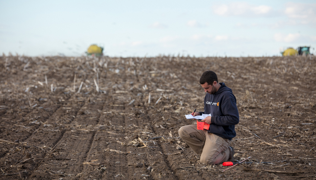 Farmer in an recently harvested field taking notes.