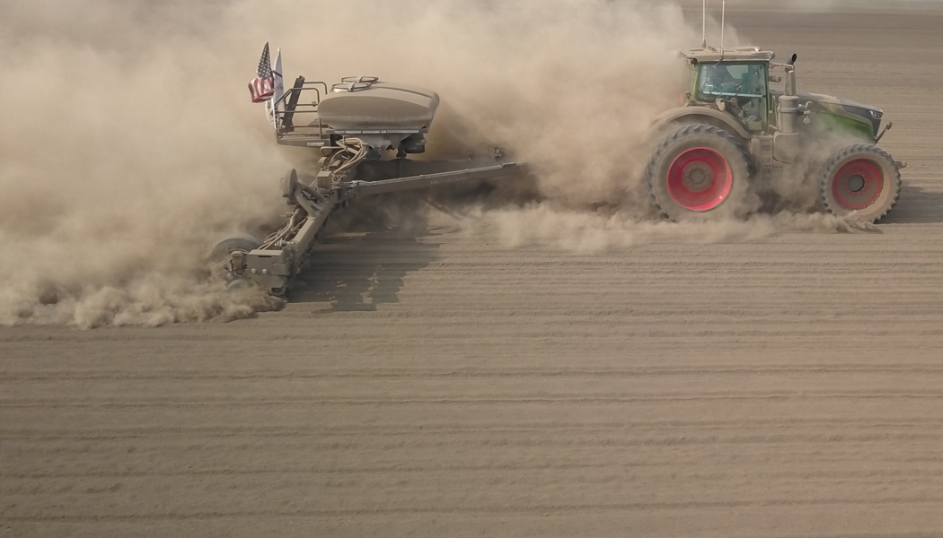 A planter moving across a dusty field.