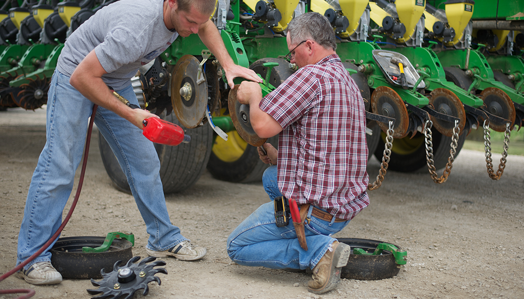 Two people fixing equipment